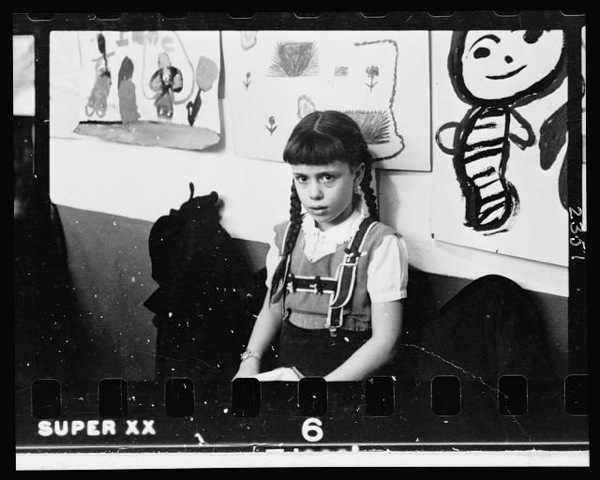 [Young girl, half-length portrait, standing against wall displaying art work, in classroom in Chicago, Illinois].jpeg