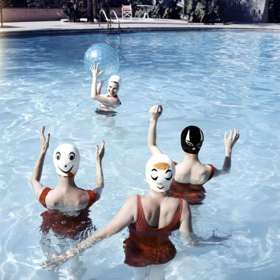 Women modeling bathing caps with faces on them.